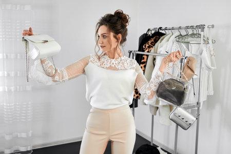 Confident European female fashion blogger presenting a handbag. Choice of wardrobe. Fashionable style