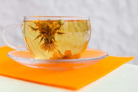 Tea. glass mug of flower tea with yellow beauty flower inside, on the table with yellow napkin - tea time