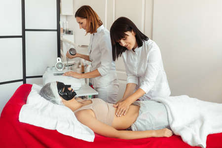 a woman in a spa salon receives a face mask and an osteopath doing a manipulative massage of a female abdomen.