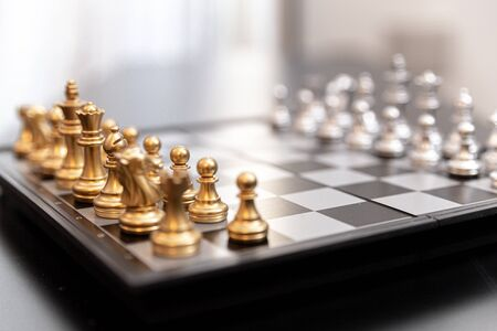 Modern chessboard gold and silver on a black coffee table 写真素材