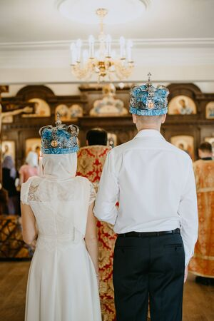 a woman and a man perform a wedding ceremony in a church in wedding crowns - view from the back - wife and husband