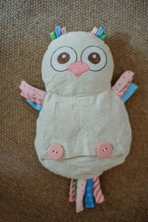 Children's toy owl - from textile lies on fabric