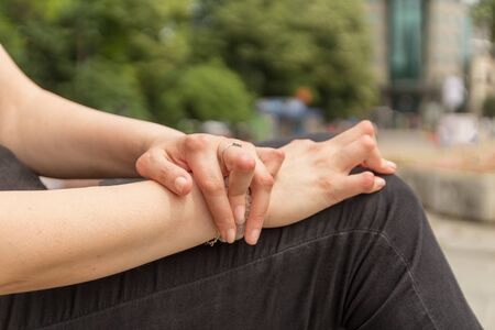 Young woman having rheumatoid arthritis takes a rest sittinng on a bench at a park. Hands and legs are deformed. She feels pain. Selected focus.