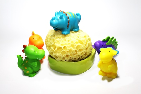 funny colored plastic dinosaurs for bathing babies with sponge photo