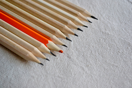 Orange Pencil Standing Out of A Large Bunch Of Pencils On A Linen Fabric Background.Stand Out Of The Crowd Concept Stock Photo