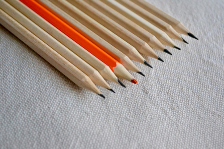Orange Pencil Standing Out Of A large Bunch Of Pencils On A Linen Fabric Background.Stand Out Of The Crowd Concept.