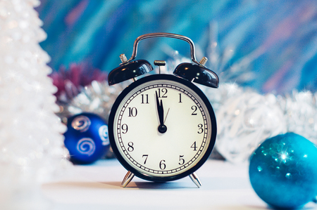 New Year alarm clock on a silver and blue background. New Year and Christmas decoration. Midnight.