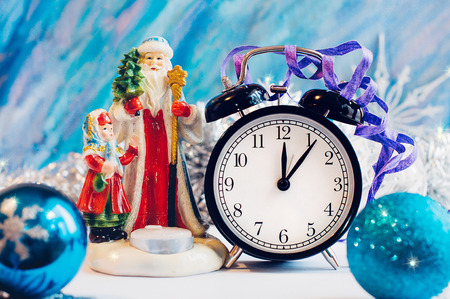 New Year alarm clock with Santa Claus and Snow girl on a silver and blue background. New Year and Christmas decoration. Midnight.