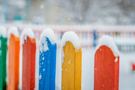 Colorful wooden fence under snow. Blue, red, yellow, orange fence parts under snow.