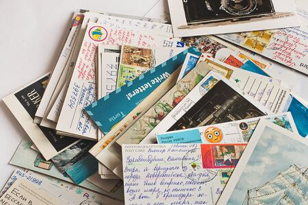 Pile of written and stamped postcards. Postcrossing footage. Postal mail. 2018. Banco de Imagens - 138050613