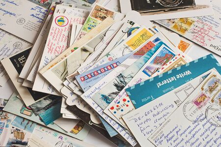 Pile of written and stamped postcards. Postcrossing footage. Postal mail. 2018. Banco de Imagens - 138050614
