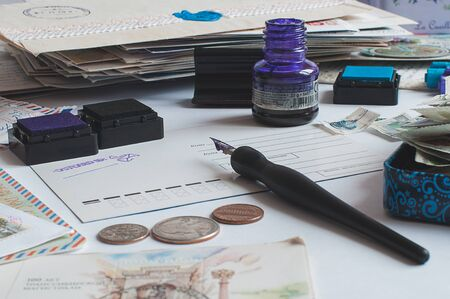 Postcrossing still life. Unwritten postcard in the center, hand writing with a fountain pen, ink, stamps, coins around.