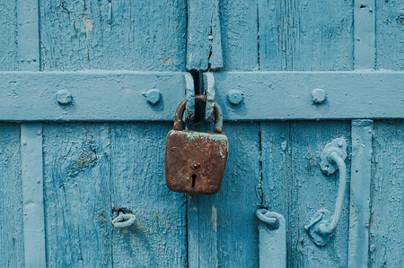 Old iron barn lock on a blue wooden doors. Archivio Fotografico