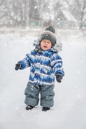 Snow flies into baby face. Little boy on snowy day playing snowballs