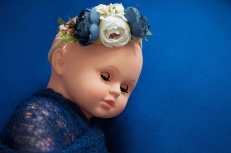 Baby doll toy photodraphed in a newborn style. Wrapped in dark blue woolen fabric on a blue background.