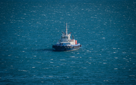 A tug ship in black sea on stormy weather. Blue water.