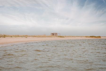 Abandoned uninhabited old wooden hut on the empty Azov sea bank, Yeisk braid island Russia.