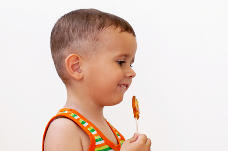 2 year old boy holding sweet lollypop in a shape of cockerel with pleasure. White background.
