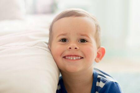 2-jähriger Junge in einem Weißlichtraum am Morgen lächelnd und umarmend Stofftier Standard-Bild