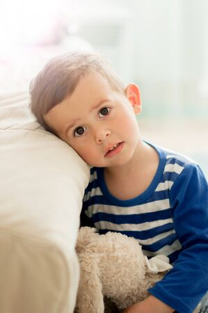 2 year old boy in a white light room in the morning embracing soft toy