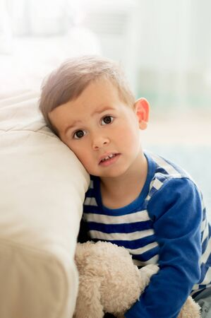 Portrait of 2 year old boy in a white light room in the morning with a sad face expression Reklamní fotografie