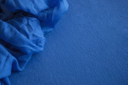 A piece of deep blue lightweight fabric lying on the blue fleece textile.