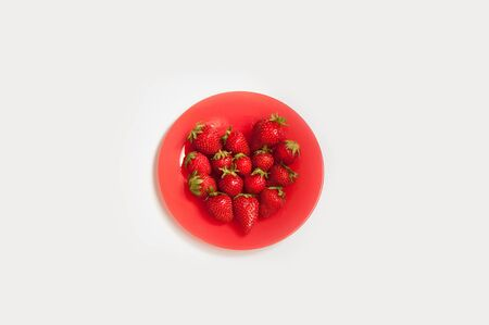Red plate with fresh strawberries laid in heart shape on white background. Archivio Fotografico