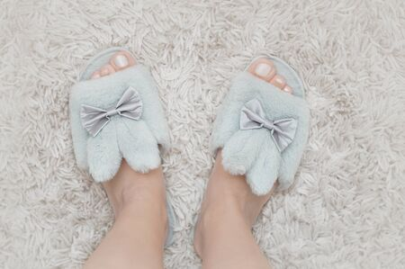 Beautiful fur slippers with ribbons in a shape of a rabbit put on women legs standing on a white furry carpet. 写真素材