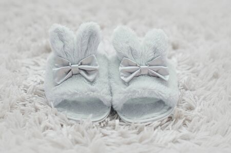 Beautiful fur slippers with ribbons in a shape of a rabbit on a white furry carpet.
