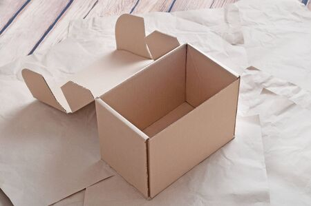 Opened carton box laying on sheets of crumpled kraft paper.