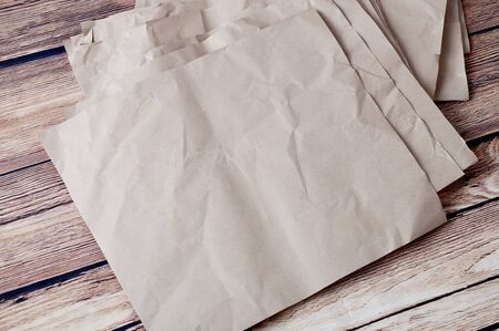 Pile of rumpled kraft paper lying in disorder on a wooden floor