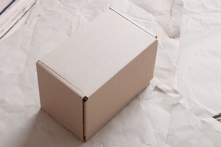 Closed carton box laying on sheets of crumpled kraft paper.
