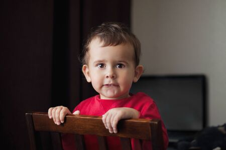 Cute 2 year old boy in a red shirt posing standing on a chair. Brown background. Archivio Fotografico - 129831640