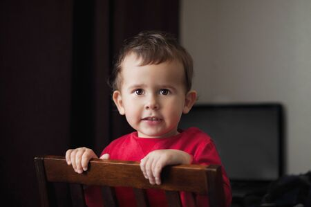 Cute 2 year old boy in a red shirt posing standing on a chair. Brown background.