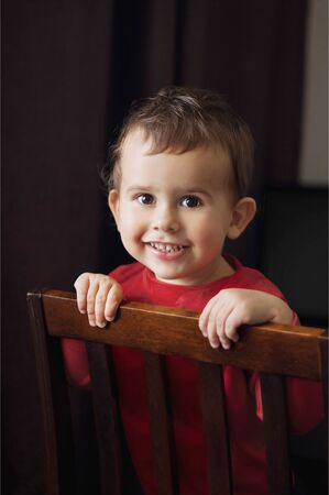 Cute 2 year old boy in a red shirt posing standing on a chair. Brown background. Archivio Fotografico - 129831649