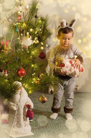 Beautiful 2 year old boy wearing christmas rabbit costume near christmas tree celebrating.