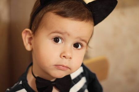 Cute 2 year old boy dressed into black cat costume ready for christmas party. Stock Photo
