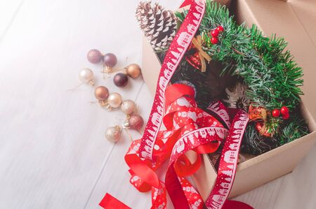Paperboard box full of christmas toys and ribbons on a white wooden floor.