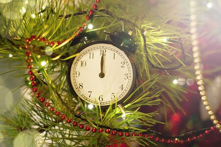New Year alarm clock lying on christmas tree branches surrounded with holiday lighs and tinsel. Midnight. Festive Chritmas background