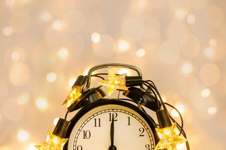 Part of New Year alarm clock wrapped into festive star garland. Midnight. Festive Chritmas background.