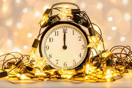 New Year alarm clock wrapped into festive star garland. Midnight. Festive Chritmas background. Reklamní fotografie
