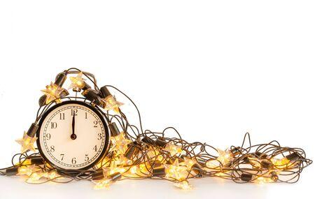 New Year alarm clock wrapped into festive star garland on white background. Midnight. Festive Chritmas background. Reklamní fotografie
