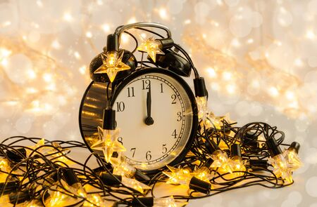 New Year alarm clock wrapped into festive star garland. Midnight. Festive Chritmas background. Stock Photo