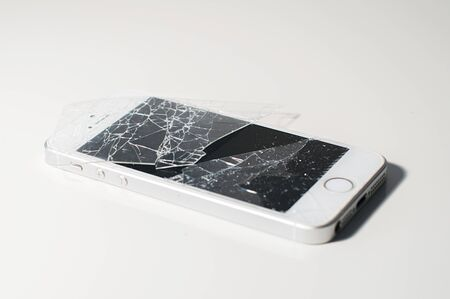 Modern smartphone with seriously broken display screen isolated on white background. Device needs repair.