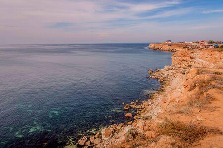 Black Sea red rocks coastline. Cape Chersonesos wild beach, Sevastopol, Russia.