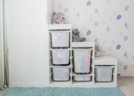 Toy storage rack in childrens's room. White furniture in real interior.