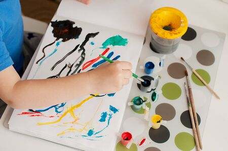 Kid's hand is painting colorful picture with gouache. Remote education concept during quarantine.