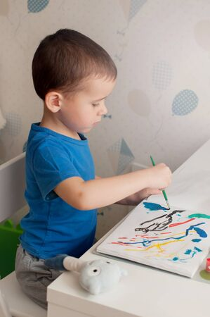 Little boy in a blue t-shirt is painting colorful picture with gouache. Remote education concept during quarantine.