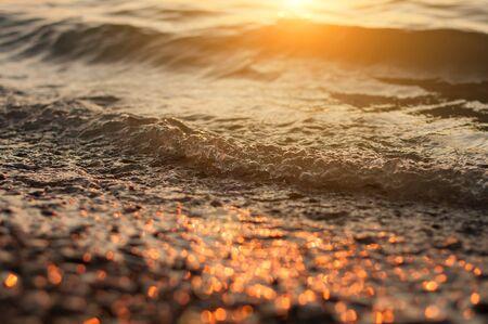 Sea surf on sunset time. Black Sea coast. Pebble washed by sea waves on sunset. Selective focus.