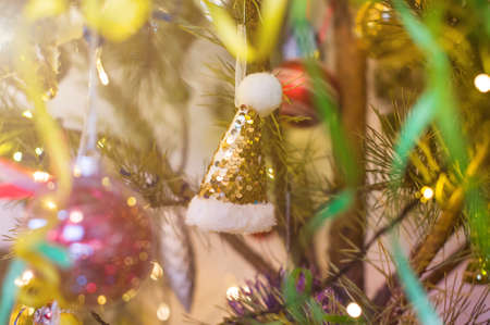 New Year and Christmas toy in a shape of golden hat hanging on a Christmas tree surrounded by other toys ans lights.
